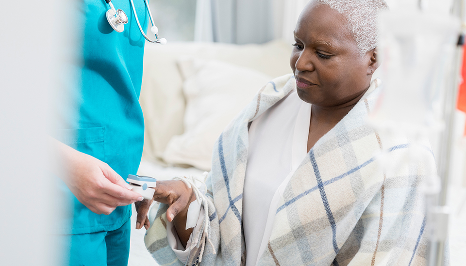 African American woman having her blood oxygen measured with a pulse oximeter